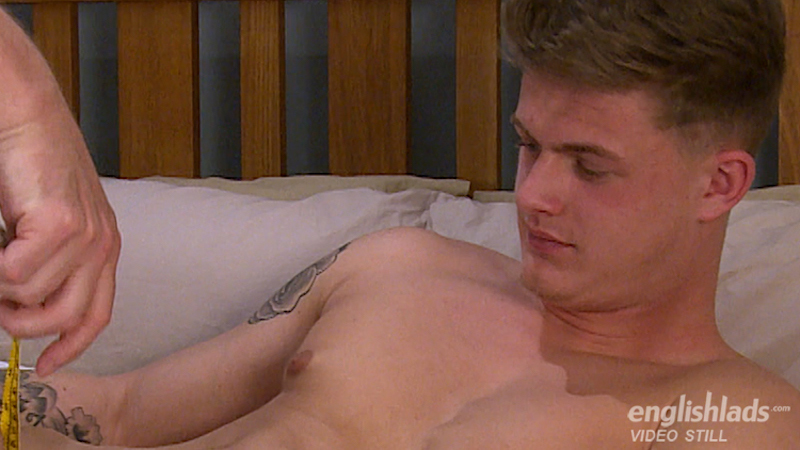 Jack Ashton lays on the bed and holds his long uncut cock upright for another man to measure