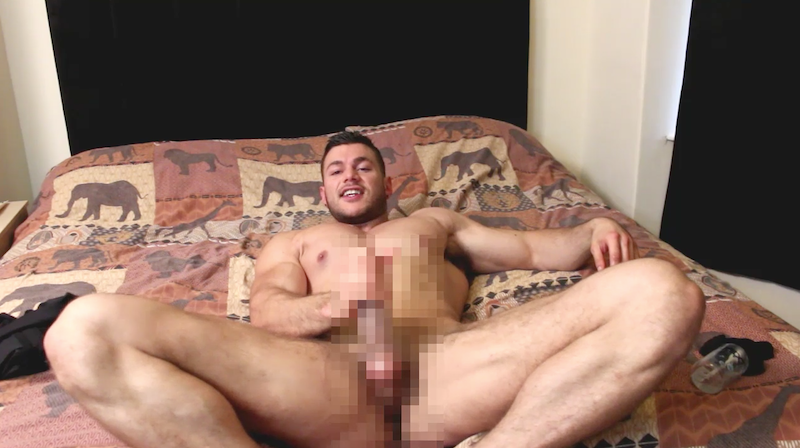 muscle man laying on a bed jerking his cock