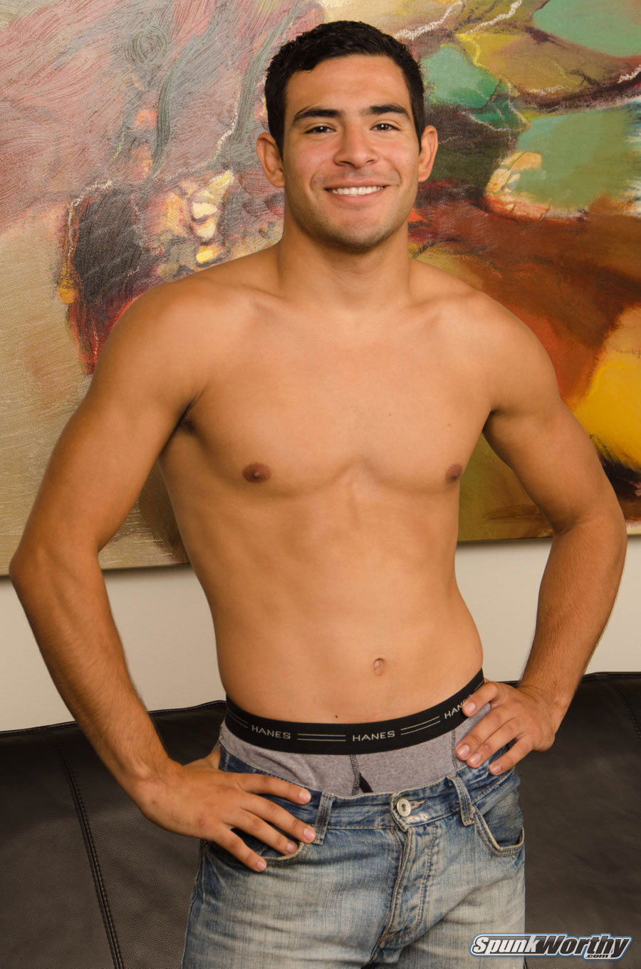 Smooth jock standing shirtless in jeans