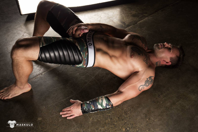 muscle man laying on the ground in Maskulo wear jerking off